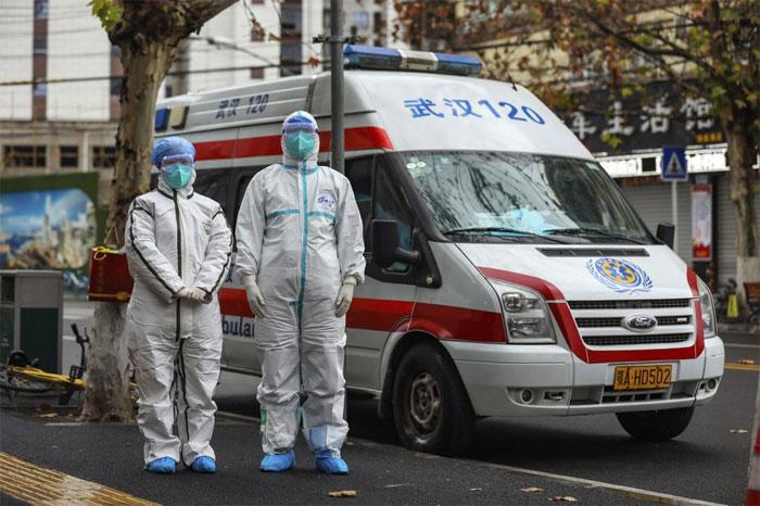 Nhân viên y tế đứng cạnh một xe cấp cứu tại Vũ Hán hôm 26/1.