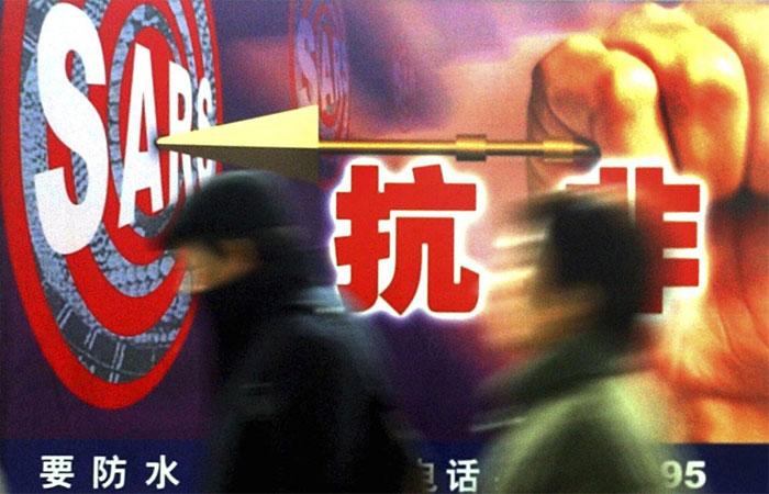 Người dân đi ngang qua một quảng cáo chống SARS ở Thượng Hải vào tháng 12/2003.