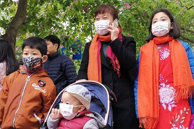 Người dân bịt khẩu trang khi tham quan hồ Gươm (Hà Nội) chiều 27/1 (mùng 3 Tết) vì lo sợ virus corona.