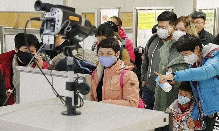 Hành khách trở về từ Vũ Hán được kiểm tra thân nhiệt bằng máy quét nhiệt ở sân bay Narita