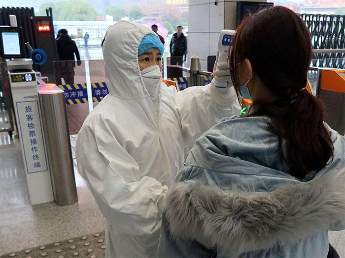 Một hành khách đang được kiểm tra nhiệt độ tại nhà ga Xianning North ở Trung Quốc.