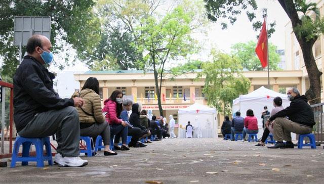 Người dân ngồi xếp hàng đợi xét nghiệm