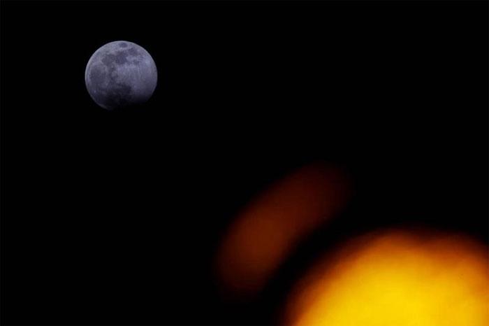 Siêu trăng xuất hiện sau cột đèn giao thông ở Vienna, Áo.