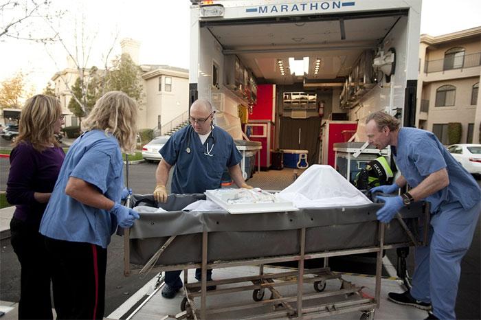 Một bệnh nhân vừa qua đời đang được các kỹ thuật viên chuẩn bị để đưa vào bể bảo quản xác