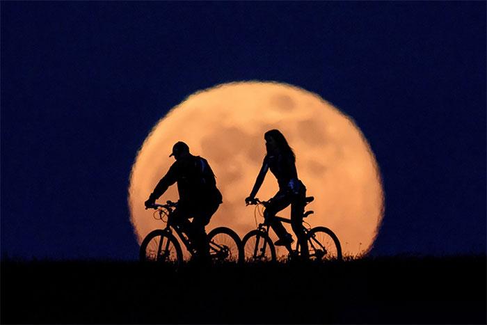 Nhiếp ảnh gia Peter Komka chụp khoảnh khắc siêu trăng mọc lên từ phía sau hai người đi xe đạp