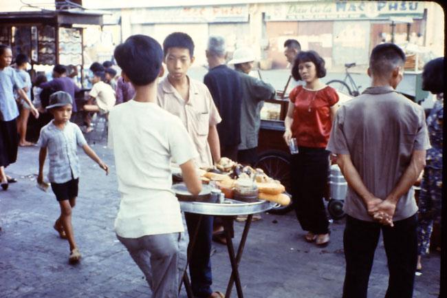 Cậu bé bán bánh mì phá lấu trên vỉa hè Sài Gòn, 1966.