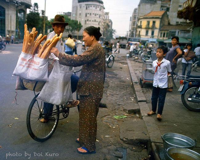 Cụ bà hớn hở mua bánh mì gần ngã tư Hồ Tùng Mậu – Hàm Nghi, 1989.
