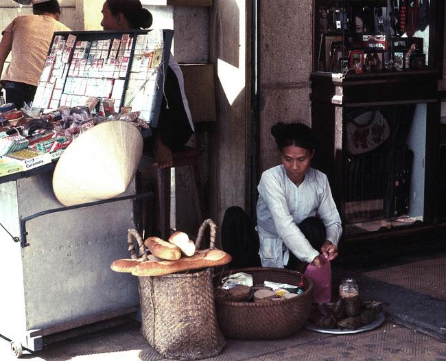 Cụ bà bán bánh mì bên vỉa hè đại lộ Lê Lợi, 1968.