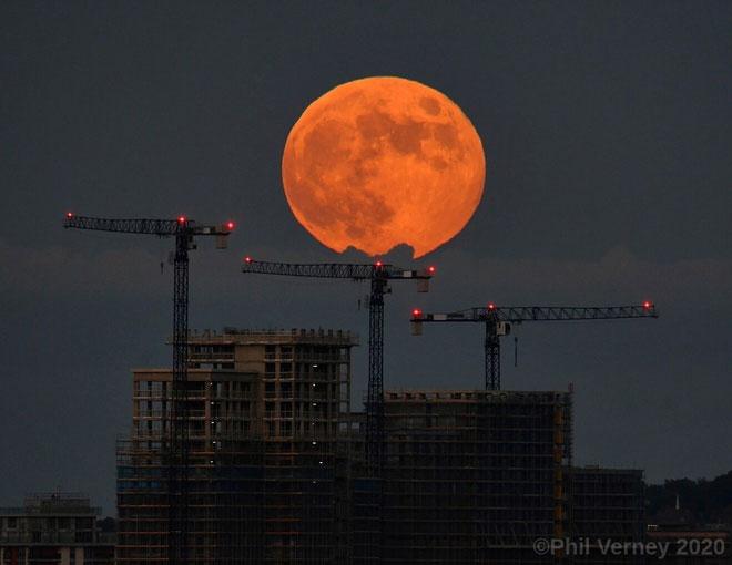 Hình ảnh mặt trăng đứng sau một công trình xây dựng tại London.