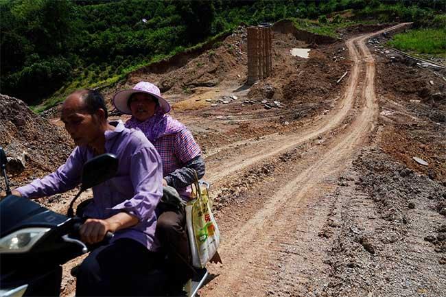 Người dân chạy xe trên một con đập bị vỡ do mưa lớn tại huyện Dương Sóc ngày 16/7.