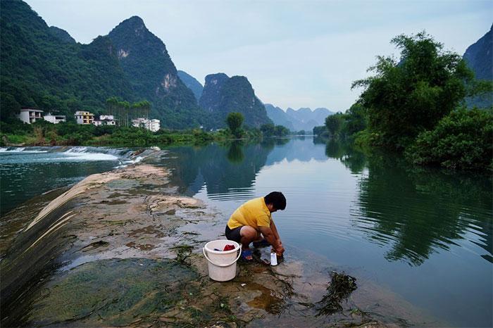 Người dân giặt quần áo tại sông Yulong, một nhánh của sông Li, tại huyện Dương Sóc ngày 17/7.