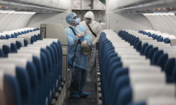 Nhân viên y tế khử trùng bên trong máy bay tại sân bay Nội Bài.