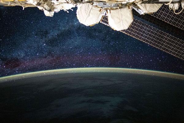 Dải Ngân Hà lấp lánh phía trên một luồng sáng khí quyển trải dài hết đường chân trời