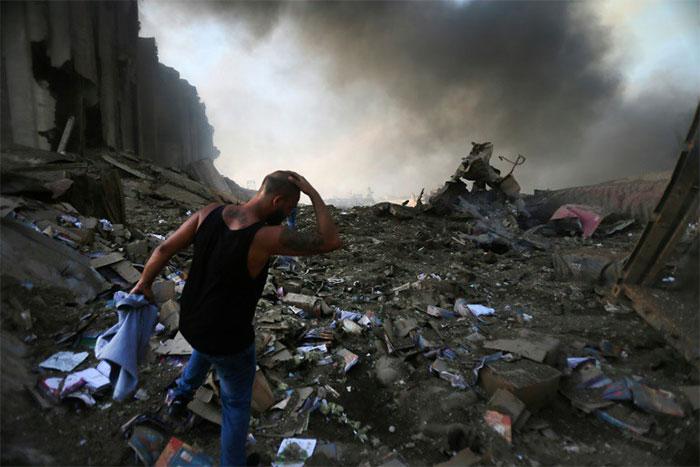 Một người đàn ông trước đống hoang tàn tại bến cảng Beirut.