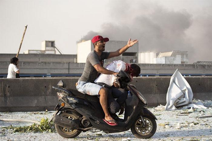 Một người đàn ông lấy xe máy để đưa một nạn nhân đi cấp cứu.