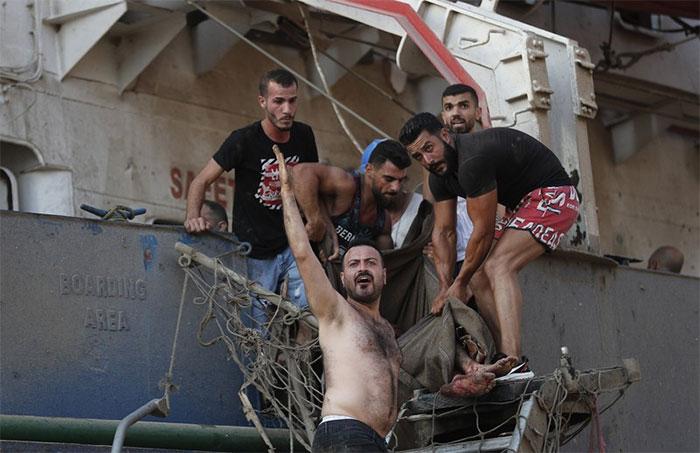 Người dân giải cứu một thủy thủ bị thương trên tàu cập cảng Beirut.