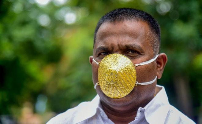 Một người đàn ông Ấn Độ sử dụng khẩu trang vàng và cho rằng nó có thể phòng ngừa Covid-19.