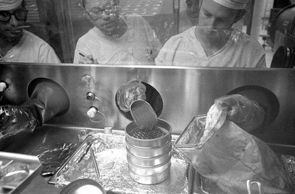 Các kỹ thuật viên làm việc với vật liệu mẫu Mặt Trăng của sứ mệnh Apollo 14 trong Phòng thí nghiệm Tiếp nhận Mặt Trăng vào năm 1971