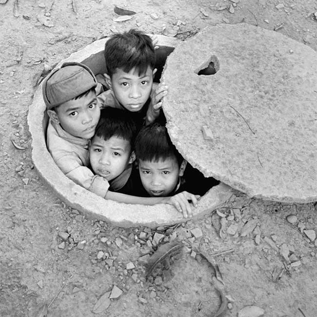 Những đứa trẻ thò đầu ra khỏi hầm tránh bom ở bên ngoài khách sạn Metropole