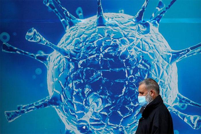 Một người đàn ông đeo khẩu trang đi ngang qua hình minh họa virus ở Oldham, Anh
