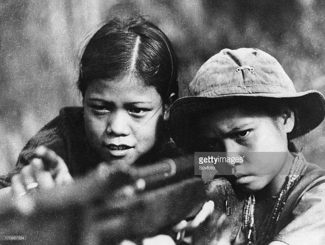 Nữ du kích nhỏ tuổi hướng dẫn em gái cách sử dụng súng