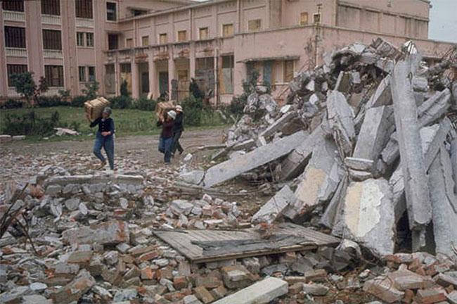Dân quân khiêng các thùng gỗ ra khỏi nhà máy xe đạp bị ném bom gần Hà Nội.