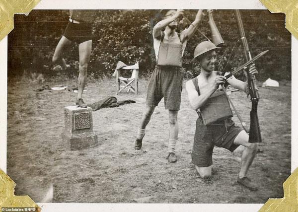 3 binh sĩ trẻ tuổi giả vờ dùng súng làm cung tên trong lúc vui đùa