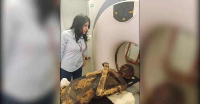 Giáo sư Sahar Saleem đứng bên cạnh xác ướp của pharaoh Seqenenre Taa II trong khi chụp CT.